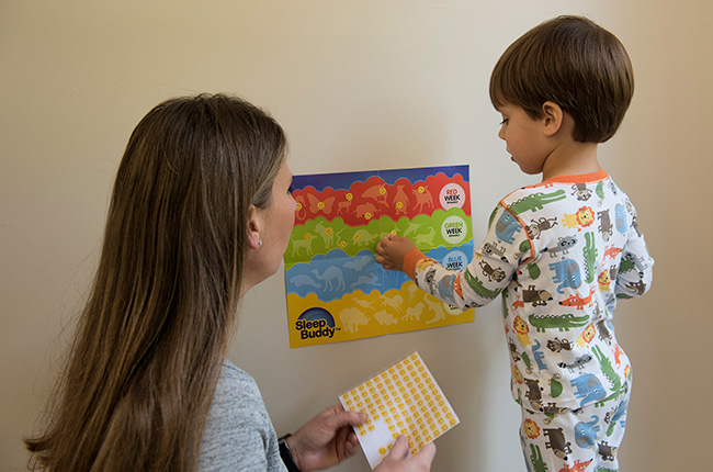 little boy putting stickers on SleepBuddy Reward Chart